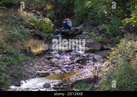 El joven se sienta solo junto a un arroyo del bosque que cubre su rostro.