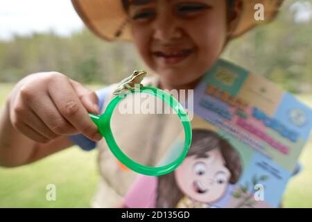 Chica mirando de cerca a una rana