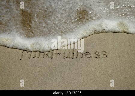 Concepto mindfulness, consciente de vivir, texto escrito en la arena de playa.