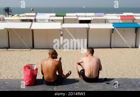 Two men eat ice creams in front of the beach of the Belgian coastal city of Blankenberge, August 6, 2009. Temperatures reached 31 degrees Celsius (88 degrees Fahrenheit) in Belgium, according to the Royal Meteorological Institute.      REUTERS/Francois Lenoir   (BELGIUM SOCIETY ENVIRONMENT IMAGES OF THE DAY) Foto de stock