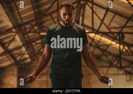 Hombre de fitness con cuerda de salto en el gimnasio en el antiguo almacén. Hombre haciendo ejercicio con saltar la cuerda en el espacio de entrenamiento cruzado.