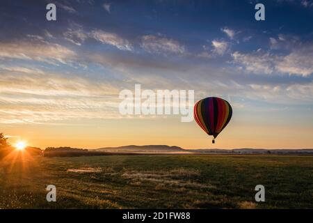 Globo de aire caliente en coloridas rayas arco iris comienza el ascenso campo de granja como el sol se eleva cielo azul nublado