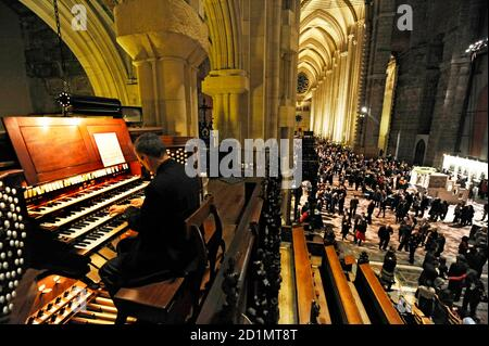 Bruce Neswick, director of cathedral music and organist, performs on the newly restored Great Organ, built in 1911 with over 8,000 pipes and 141 ranks, as thousands of people party in the 601-foot-long church. The  church was open for an 'End-to-End' party celebrating the completion of a seven-year restoration project after the organ and interior had been damaged by a December 2001 fire.  REUTERS/Ray Stubblebine  (UNITED STATES)
