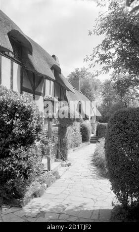 CASA DE ANNE HATHAWAY, Shottery, Stratford upon Avon, Warwickshire. Anne Hathaway's Cottage en Stratford-upon-Avon, mirando a lo largo del camino en el frente de la cabaña. Esta casa de entramado de madera data en parte del siglo 15. Fotografiado por Eric de Mare entre 1945 y 1980.