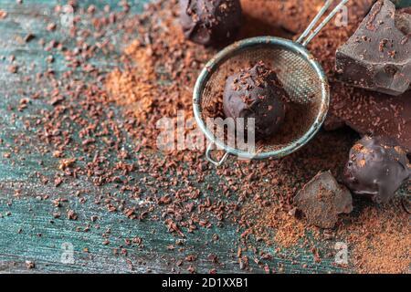 Deliciosas trufas de chocolate con cacao en polvo y chocolate negro sobre un fondo de madera oscura.
