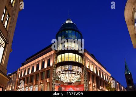 Fachada moderna iluminada del centro comercial 'Schadow-Arkaden' en el centro de Düsseldorf, Alemania, durante la época navideña.