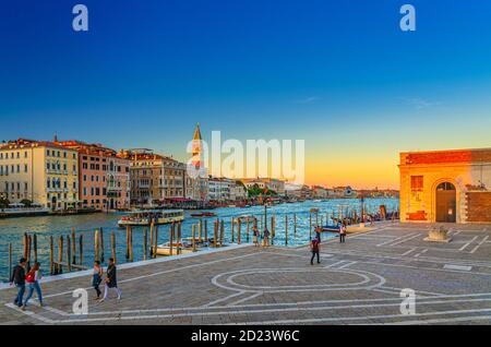 Venecia, Italia, 13 de septiembre de 2019: Fondamenta Salute terraplén paseo cerca del muelle de la vía fluvial del Gran Canal al atardecer, campanario Campanile y fila de edificios de estilo barroco en San Marco Sestiere