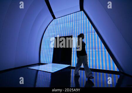 Una mujer pasa por delante de una obra de arte llamada 'Untitled 2008' del artista francés Daniel Buren en el futurista pabellón creado por el arquitecto deconstructivista británico-iraquí Zaha Hadid para la exposición de Chanel 'Mobile Art', en el distrito central de Hong Kong el 26 de febrero de 2008. Hong Kong, Tokio, Nueva York, Londres, Moscú y París son las paradas de la gira internacional, exhibiendo las obras de 20 artistas contemporáneos internacionales. REUTERS/Victor Fraile (CHINA)