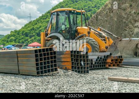 Reparación de las comunicaciones urbanas. Excavadora amarilla en un sitio de construcción en un día soleado con tuberías rectangulares