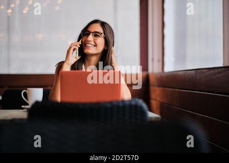 Una empresaria encantada trabajando remotamente en el café mientras discutía negocios problemas con el smartphone y sentarse en la mesa con el ordenador portátil