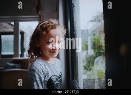 Retrato de una chica sonriente de la escuela de pie cerca de la ventana con lluvia gotas en la ventana en la temporada de lluvias Foto de stock