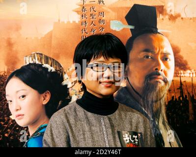 Chinese director Hu Mei poses in front of a poster featuring Hong Kong actor Chow Yun-fat (R) and Chinese actress Zhou Xun during a news conference of their movie 'Confucius' in Hong Kong January 25, 2010.   REUTERS/Bobby Yip  (CHINA - Tags: ENTERTAINMENT)