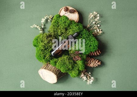 Vista superior del frasco con pipeta en musgo verde sobre fondo verde. Medicina alternativa, esencia de hierbas, concepto de estilo de vida sostenible.