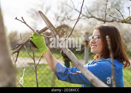 Mujer jardinera en guantes con sierra de jardín corta ramas
