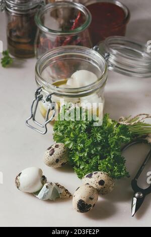 Ingredientes para el marinado en escabeche casero huevos de codorniz. Huevos en caja de plástico, la salsa de tomate, pimientos, anchoas en tinajas, verdes frescos, tijeras, ol