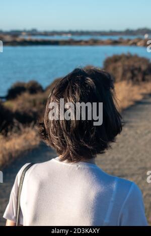 Primer plano del cabello marrón de una joven de atrás que se despierta en un parque con un bonito lago en el lado izquierdo. Foto de stock