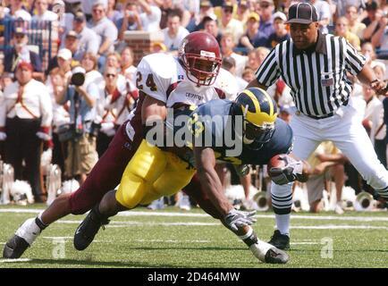 El regreso de la Universidad de Michigan Chris Perry (23) se sumerge en un touchdown con el Central Michigan James King (24) fallando en detenerlo en el segundo cuarto del juego en el Michigan Stadium en Ann Arbor, 30 de agosto de 2003. REUTERS/Rebecca Cook RC