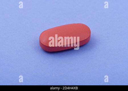 Forma ovalada tableta de medicina farmacéutica sobre fondo azul, Lay plano. Espacio de copia. Conceptos de medicina. Concepto abstracto minimalista. Color azul claro