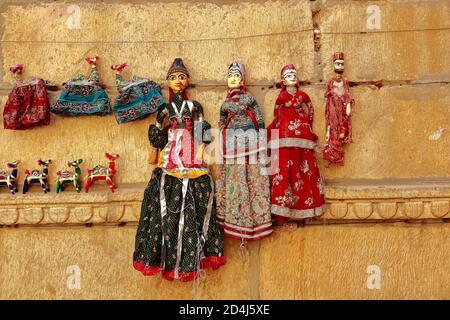 Marionetas coloridas con forma humana con ropa de colores colgando contra el Muro en Rajasthan India el 21 de febrero de 2018