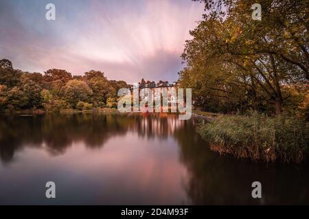 Una larga exposición del otoño se reflejó sobre un estanque en Hampstead Heath, Londres, Inglaterra.