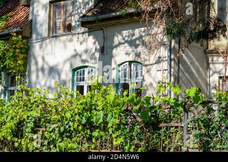 Fachada de una antigua casa con ventanas y azulejos de madera. casa del siglo 19 sin restauración.