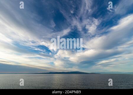 En la distancia una formación de nubes sobre el agua y una pequeña isla.