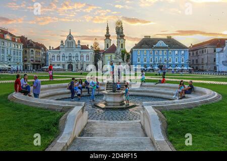 Timisoara, Romani - 2 de agosto de 2016 escena puesta de sol en la Plaza Unirii (Plaza Unión), Timisoara, Rumania se centra en la fuente central con la gente disfrutar