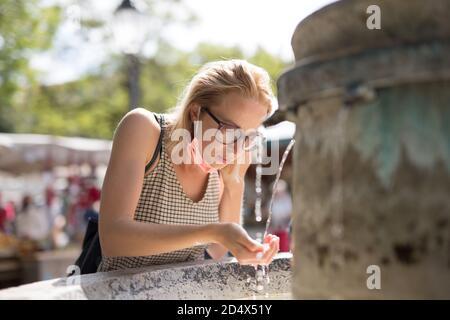Mujer cucasiana joven y sedienta con mascarilla médica que bebe agua de la fuente de la ciudad pública en un caluroso día de verano. Nuevas normas sociales durante
