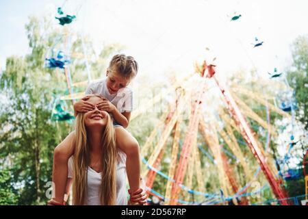 La hija se sienta sobre los hombros. Alegre niña su madre se lo pasara bien en el parque junto a las atracciones