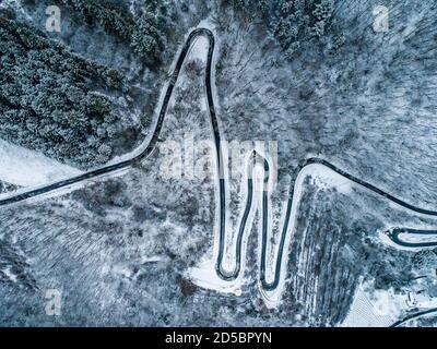 Estaciones concepto invierno nieve Vista aérea Winding carretera serpentina montaña pasar pueblo Brodenbach Alemania.