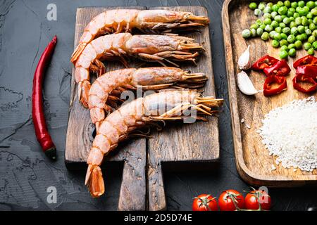 Paella tradicional valenciana ingredientes de mariscos con gambas, mejillones, arroz y especias sobre superficie de concreto negro