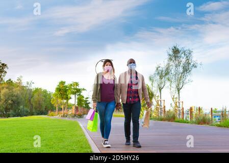 atractiva pareja interracial usando máscara de cara sosteniendo las manos con las compras bolsas de papel mientras caminaba en un parque en otoño.concepto alrededor la nueva normalidad