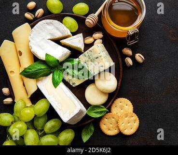 Varios tipos de queso sobre un fondo de concreto negro