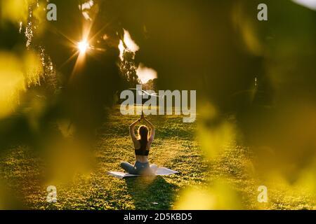 Visión remota de la mujer flexible levantando los brazos, plegándolos juntos por encima de la cabeza en la postura de Namaste.