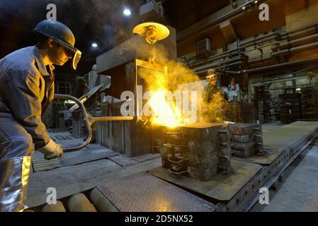Los trabajadores en una pieza de metal de fundición - Seguridad en el trabajo y el trabajo en equipo