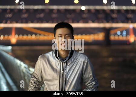Foto mediana de un joven asiático mirando la cámara por la noche. Sonriendo feliz. El puente del río Wuhan Yangtze se ha desenfocado como fondo