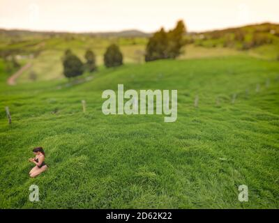 Mujer meditando en un campo de hierba vacío.