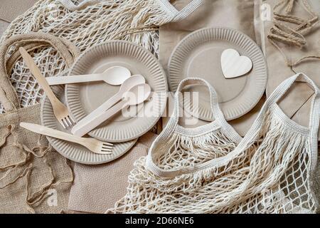 Conjunto de productos ecológicos, cero residuos, sin plástico y concepto ecológico. Papel desechable vajilla, cubiertos de madera, bolsa de malla de algodón reutilizable, vista superior.