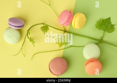 macarons horneados de varios colores redondos, el postre se encuentra sobre un fondo verde amarillo, vista superior. Foto de stock