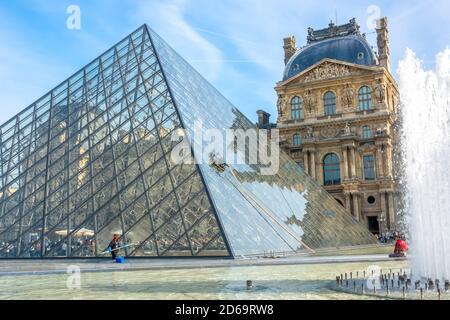 Francia, París. Día soleado de verano en el patio del Museo del Louvre. Lavado manual y automático de la pirámide de cristal. Fuente y turistas.