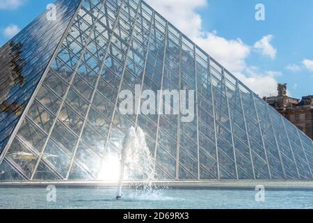 Francia. Día soleado en París. Pirámide de cristal y fuente en el patio del Museo del Louvre de cerca.