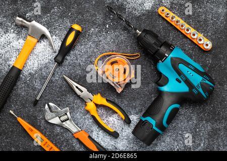 Conjunto de herramientas sobre un fondo oscuro. Concepto de renovación, tareas domésticas. Composición plana. Taladro eléctrico, destornillador, cinta métrica, llave, cuchillo y h