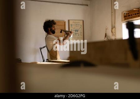 Hombre hispano trabajando como carpintero en un pequeño laboratorio de madera. El hombre barbudo se concentró en dar forma a una nueva pieza de madera para un mobiliario de casa en su ca
