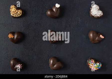 Pralinas de chocolate aisladas sobre un fondo oscuro. Vista superior, disposición plana.