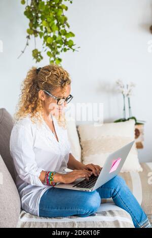 Una mujer hermosa trabaja y se relaja en casa con un ordenador portátil ordenador - concepto de trabajo inteligente y oficina alternativa - las mujeres disfrutan de la tecnología en el sofá