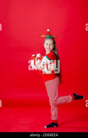 Retrato de una chica alegre divertida con un vendaje de cuernos en la cabeza abrazando a un oso de peluche en Navidad pijama aislado sobre un fondo de color rojo brillante. T
