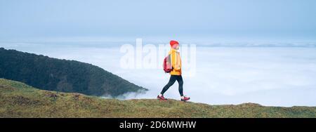 Joven mujer mochilero vestido chaqueta impermeable naranja senderismo por la montaña por encima de la ruta de la nube a finales de febrero en la isla de Madeira, Portug Foto de stock