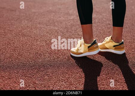 Mujer joven activa en zapatillas haciendo ejercicio por la mañana