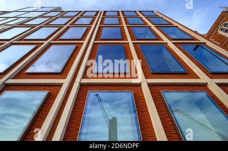 Un edificio de oficinas en Londres con ladrillos rojos y ventanas azules. Las líneas rectas dan una fuerte perspectiva hacia arriba. Reflejos de grúas en las ventanas.