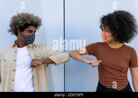 Anónimo joven afroamericano hombre y mujer con pelo rizado en ropa informal y máscaras protectoras que tocan los codos contra el blanco pared